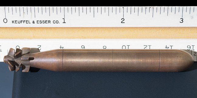 This brass torpedo is about three inches long and seems to be solid. It doesn't have any markings.