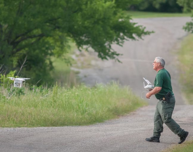 Sheriff John Christian launches his drone to search the woods for a shooting suspect last night in Byng.