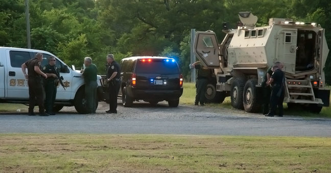 Police officers, including Pontotoc County Sheriff John Christian (green shirt), employ the tools of their trade, including an unmanned aerial vehicle and a military surplus Mine-Resistant Ambush Protected (MRAP) vehicle to apprehend a suspect in a shooting last night.