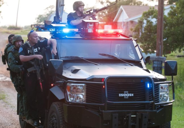 Officers ride on the running board of an armored vehicle after clearing a house during the search for a shooting suspect in Byng last night.