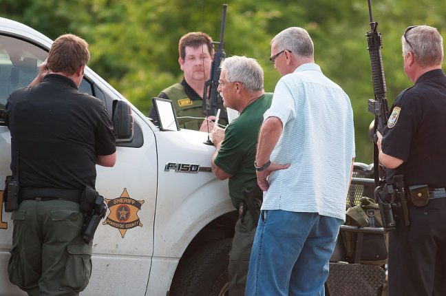 Pontotoc County Sheriff John Christian and Ada Police Chief Mike Miller, surrounded by officers and deputies from several agencies, work to find a fugitive during a May 2016 manhunt in Byng less than half a mile from our home.
