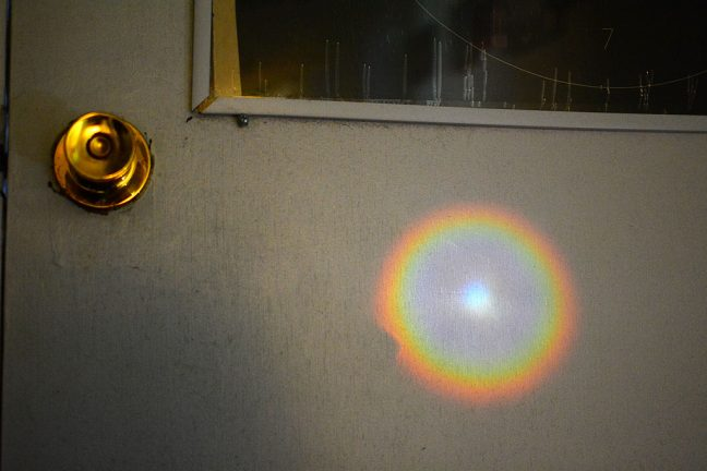 Light from our peephole shines all the way down the hall to the back door of our house this morning.