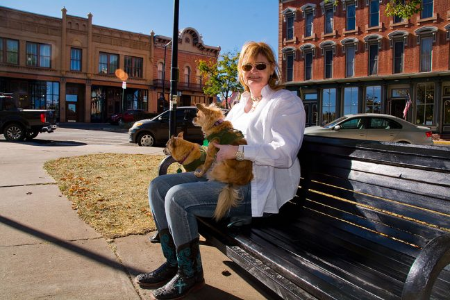 "Abby sits on a park bench in Las Vegas, New Mexico's historic Old Town Plaza, location of filming of one of her favorite television shows, ""Longmire."" Over her right shoulder is the building that acts as the Absaroka County, Wyoming Sheriff's Office. The door still bears the logo from the show set in Durant, Wyoming, but filmed entirely in New Mexico."