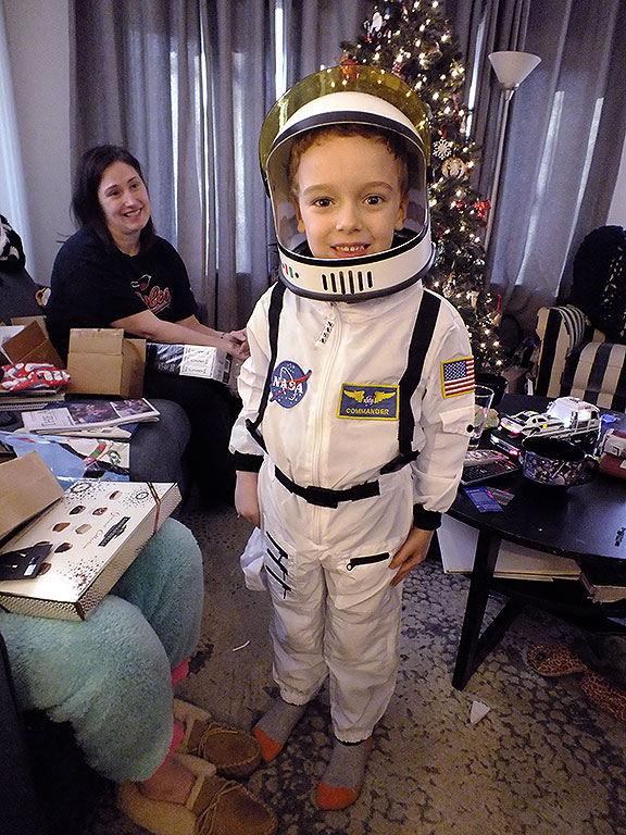 Paul smiles on Christmas morning as he tries on his new NASA flight suit, a gift from Abby and me.