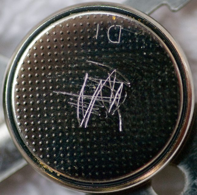 Scoring the surface of the new button cell will help the solder cling to it.