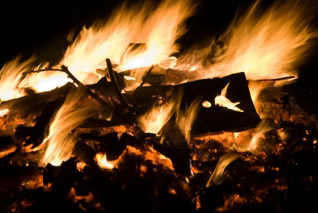 A light breeze carries away heat and flames from my brush pile fire tonight.