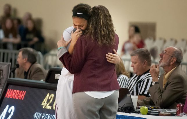 Ada senior Maddie Jessepe hugs coach Christie Jennings in the waning seconds of Friday's semifinal game against rival Harrah.