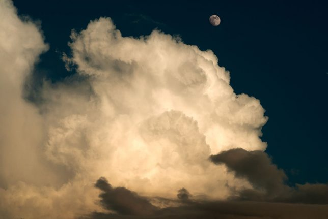 The moon slides over the top of a small, brief thunderstorm in Byng two nights ago.
