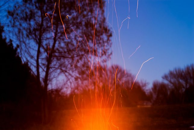 Sparks fly above the brush pile fire on the pond last night.