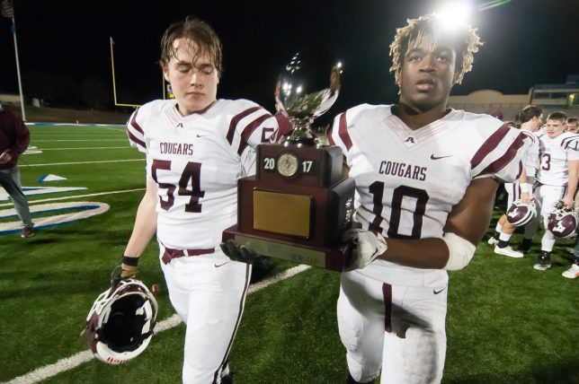 Seniors A.J. Steele and Grant Bellard carry the silver runner-up trophy to the fans Friday night. As bitter as it is to accept the defeat it represents, it is an amazing achievement to receive the runner-up title.
