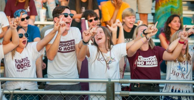 Ada Cougar football fans raise their hands in anticipation of the opening kickoff Friday, Aug. 31, 2018 against Ardmore at Noble Stadium. The Cougars lost the season-opener 33-7.