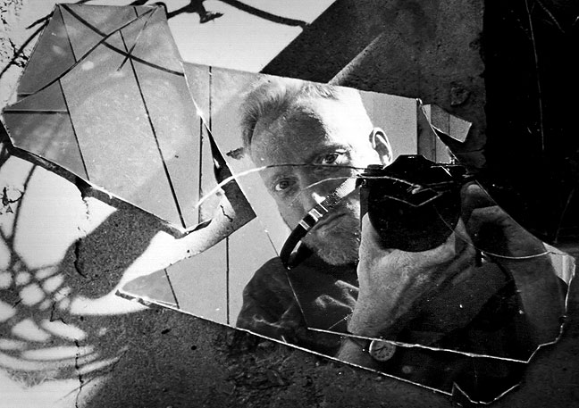 "This is one of my all-time favorite self portraits, in a mirror on the ground at the so-called ""Plague Town"" along Interstate 40 in eastern New Mexico."