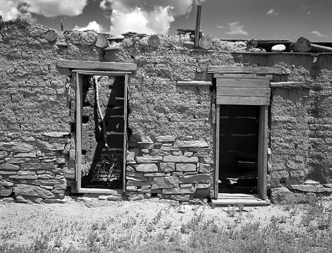 An abandoned house stands in midday light along New Mexico highway 3.
