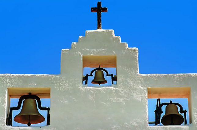 The bells of the Tularosa Mission Church stand against a perfect blue sky.