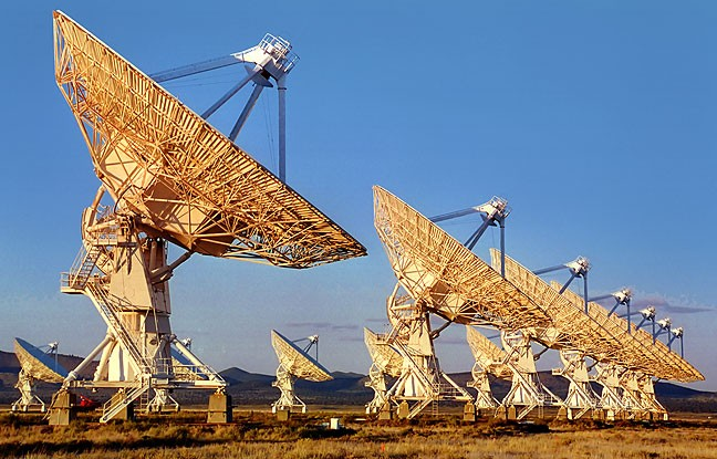 The white dishes of the Very Large Array's antennas pick up colorful evening light.