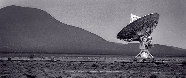 Lone radio telescope antenna set against the Magdalena Mountains.