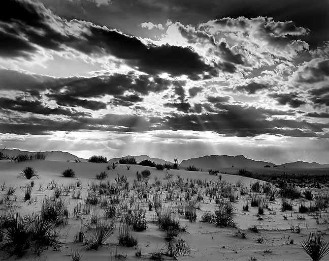 Crepuscular rays shine though clouds at White Sands National Monument.