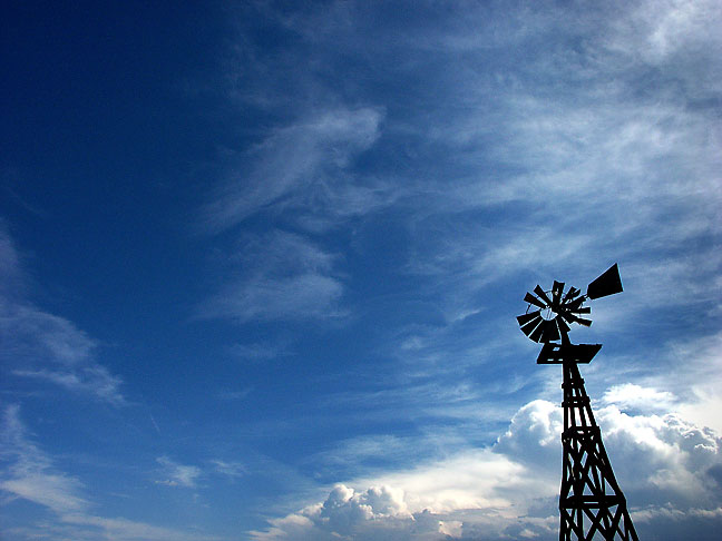 A windmill is set against an approaching thunderstorm just outside Caprock park boundary.