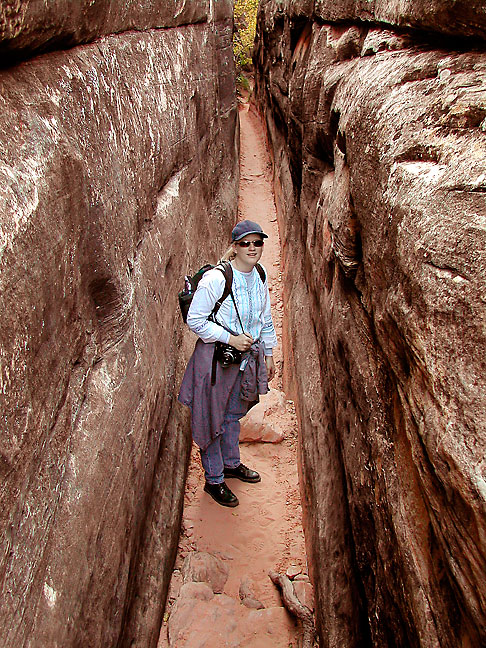 "Jamie makes her way down ""the crack,"" a narrow passage on the way to Chesler Park at Canyonlands."