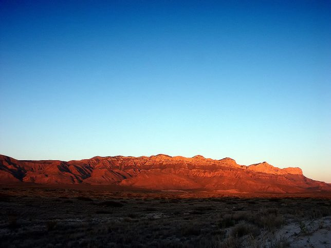 After the sun set on the gypsum dunes, it continued to shine on the much taller mountains, creating this deep blue and amber moment.