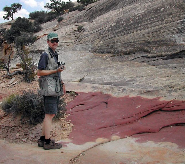 The author turns to smile at Abby's camera as the two hike down to Sipapu Bridge at Natural Bridges National Monument.