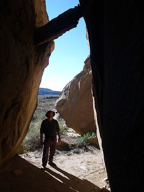 David stands under a stone in gap on the easternmost trail at Chaco, Wijiji.