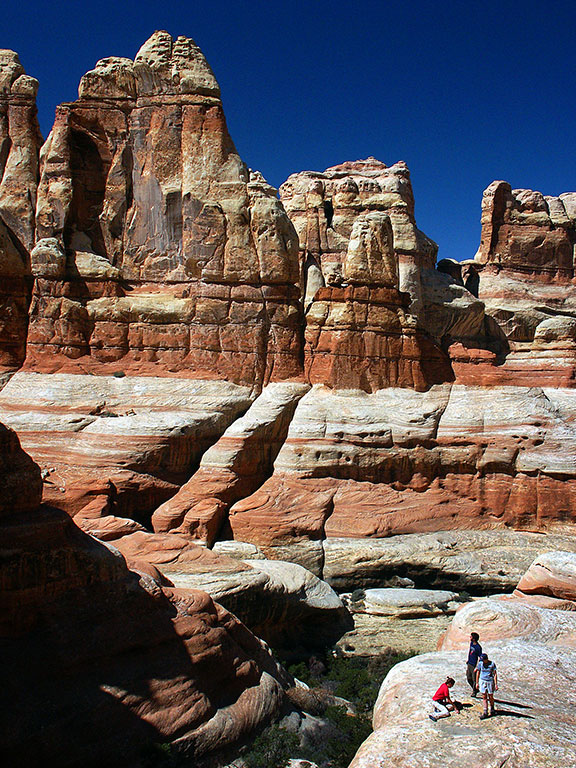 Visitors are dwarfed by Cedar Mesa sandstone at Druid Arch.