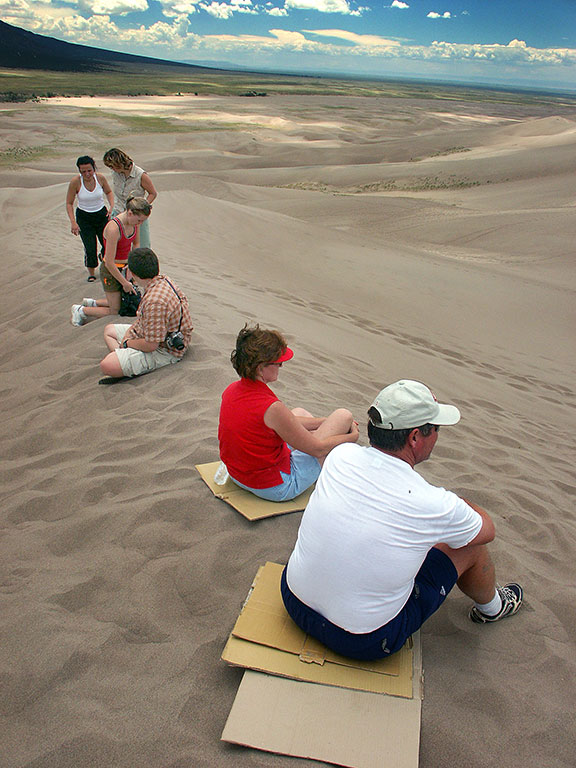 Visitor sit on cardboard during the day at Great Sand Dunes. Unlike White Sands in New Mexico, darker sand gets very hot in the sun.