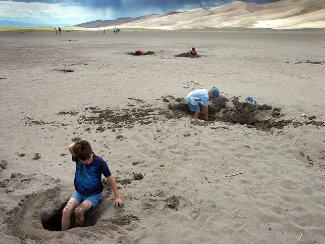 Children play in the sand flat near Medano Creek at Great Sand Dunes. It could be thought of as the ultimate sandbox.