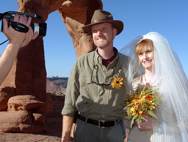 Abby and I smile as we exchange wedding vows at the majestic Delicate Arch in Utah's Arches National Park.