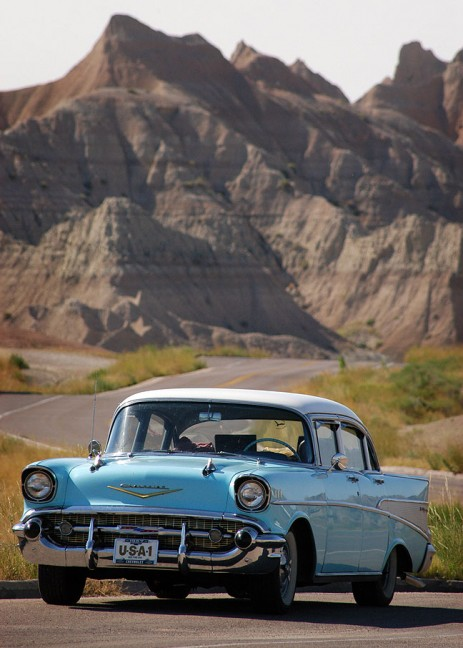 A classic Chevrolet sits by the side of the main road through Badlands National Park.
