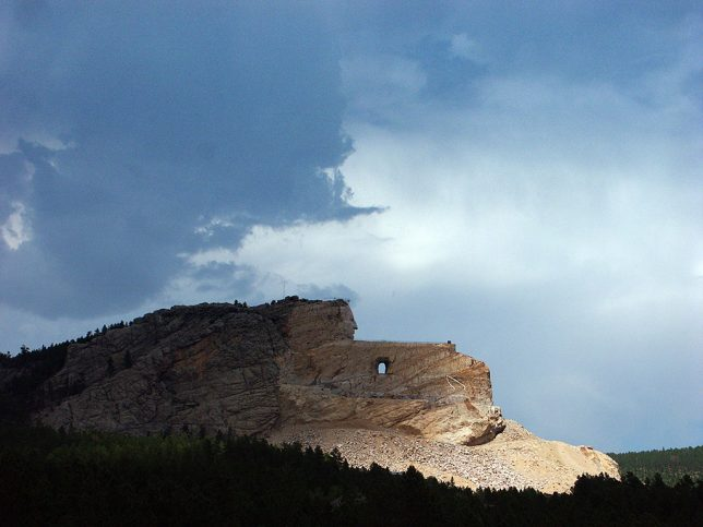 This broad view of the Crazy Horse Memorial shows its enormity beneath a thunderstorm.