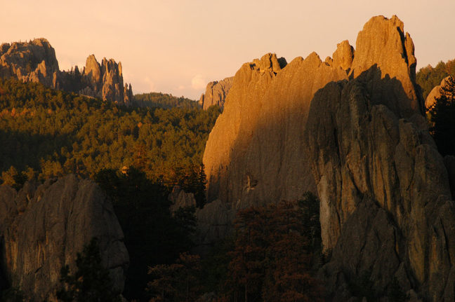The shadows of sunset creep up on distant formations of the Needles Highway at Custer State Park.
