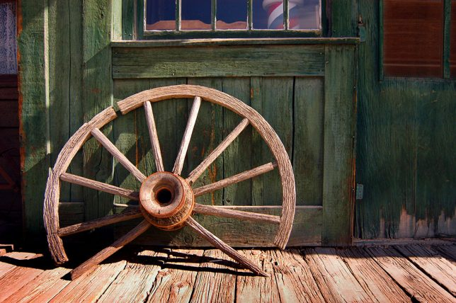 A broken wagon wheel sits on the wooden boardwalk of Ogallala, Nebraska's old west display.