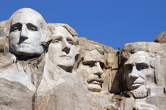 Workers rappelling on lines with power washing equipment are visible in this Mount Rushmore image.