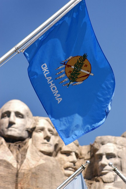 The flags of all 50 U. S. States, including ours, Oklahoma, are displayed at Mount Rushmore.