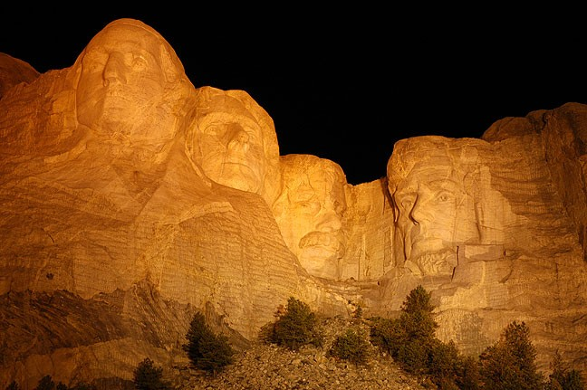 The faces on Mount Rushmore are illuminated by deep amber light during the nighttime ceremony at the Monument.