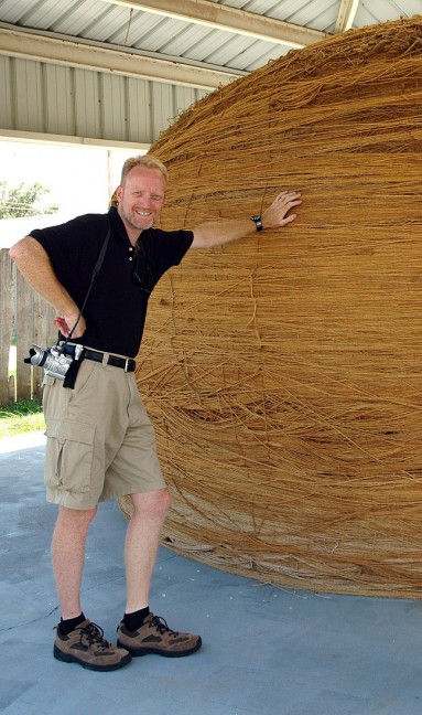"The author leans on the world's largest ball of sisal twine in Cawker City, Kansas. As Abby pointed out in a video clip from the day, ""This is not a haystack."""