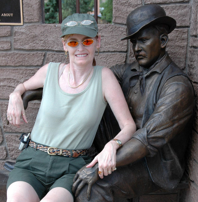 Abby smiles as she poses with the bronze statue of The Sundance Kid in Sundance, Wyoming.
