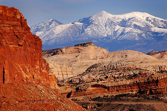 This view looks east from Capitol Reef's Rim Overlook Trail, showing the Waterpocket Fold and, in the distance, the Henry Mountains.