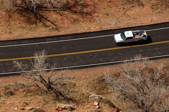 A vehicle passes on the roadway 1500 feet below.