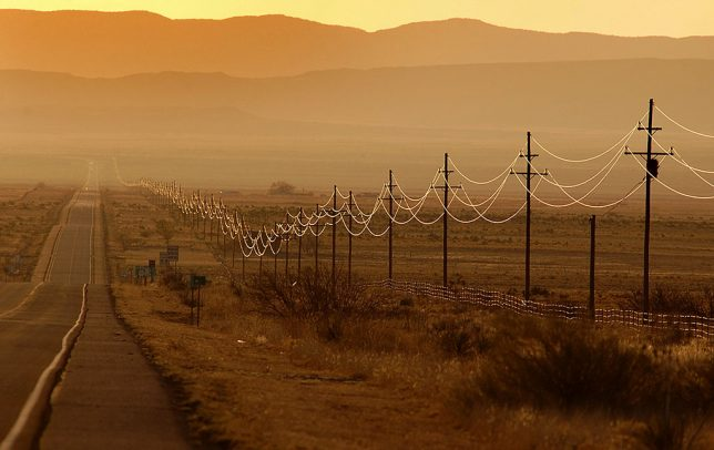 The sun rises on power lines on U.S. 380 in New Mexico's forbidding Journada del Muerto Desert, home of the Trinity Site where the first atomic bomb was tested.