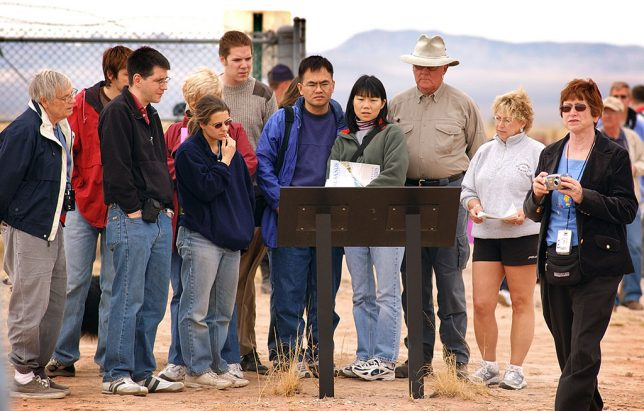 A group of tourists read a kiosk at the Trinity site.