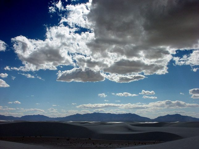 Clouds hide the sun monetarily in this view of White Sands with the San Andres Mountains in the distance.