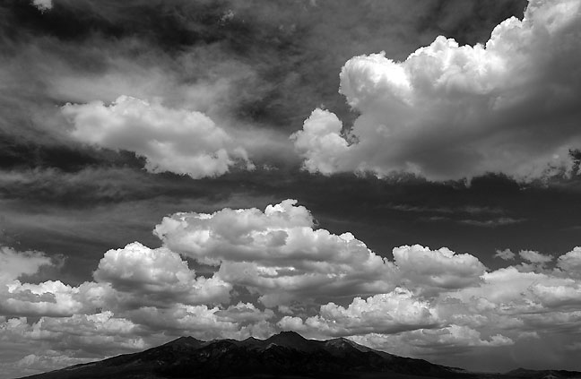 Clouds and the summer sky dwarf the 14,351-foot Blanca Peak at the south end of there Sangre de Christo Mountains of Colorado.