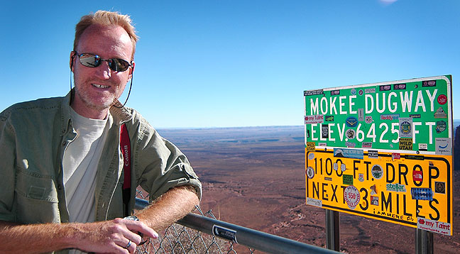 Your host poses at the sign at the top of the Mokee Dugway. Just three years earlier, this sign had no stickers on it.