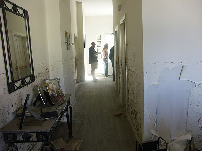 Nicole stands at the end of her hallway about a month after Hurricane Katrina flooded her home.