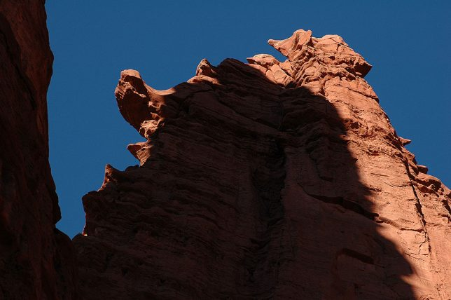 The reddish brown mudstone of Fisher Towers and deep shadows are set against a perfect blue sky.