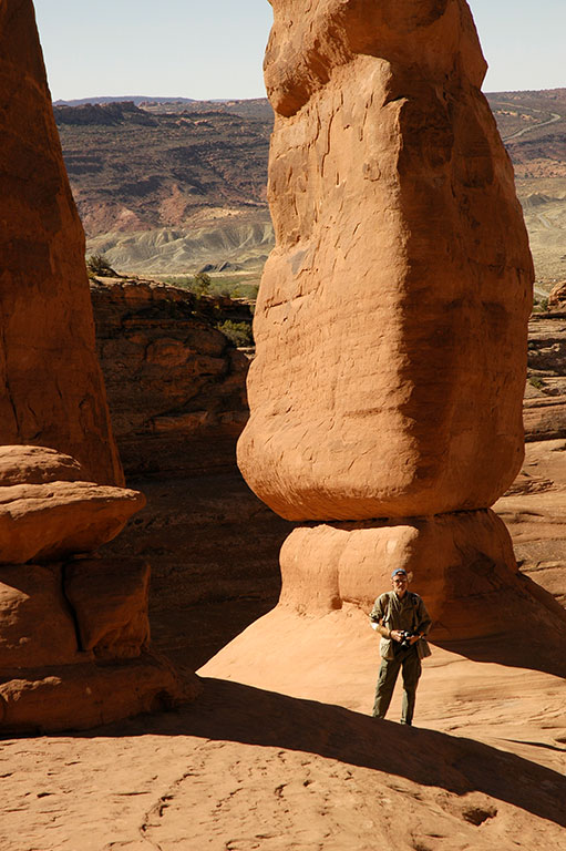 Posing under Delicate Arch, the author attempts to provide a sense of scale.