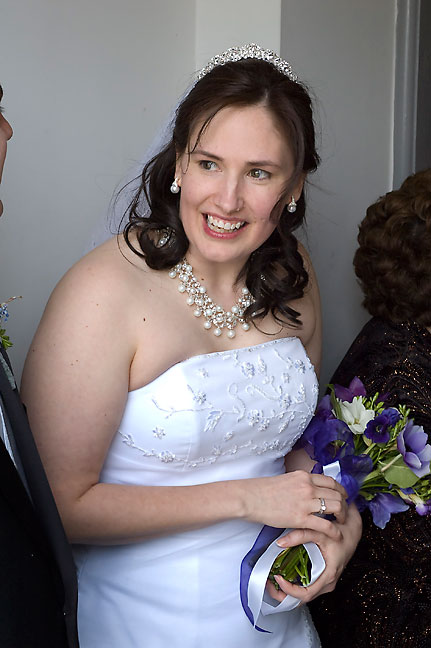 Chele smiles as she greets friends and relatives in the receiving line after the service. Because of the light and the incredible look on her face, I view this as my favorite photo from the wedding.